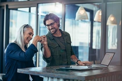 En ung forretningsmand og en ældre forretningskvinde giver hinanden et knytnæveslag på kontoret. Forretningskolleger ser glade og begejstrede ud efter afslutningen af et projekt.