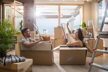 Unge, glade par sidder i kartonkasser i deres nye hjem og har det sjovt, mens de spiller badminton.